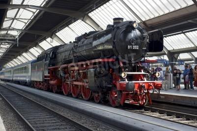Poster Zurique, Suíça - 04 de junho de 2011: Um trem com um renovado Pacífico 01 202 locomotiva a vapor está pronto para partir da estação principal de Zurique (Hauptbahnhof).