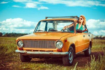 Quadro A mulher está conduzindo um carro amarelo velho. Fundo rural.