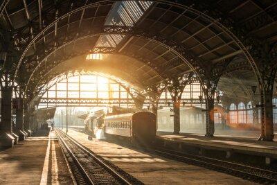 Quadro Antiga estação ferroviária com um trem e uma locomotiva na plataforma aguardando a partida. Raios de sol da noite em arcos de fumaça.