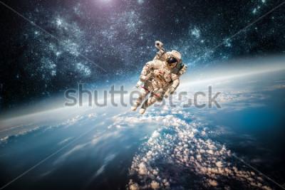 Quadro Astronauta no espaço exterior contra o fundo do planeta Terra. Elementos desta imagem reduzida pela NASA.