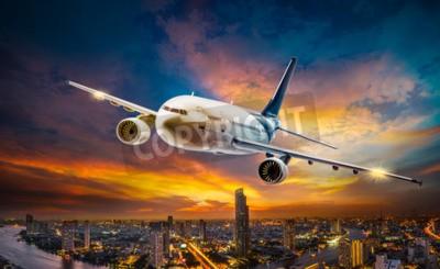 Quadro Avião para o transporte que voa sobre a cidade da cena noturna no fundo do pôr-do-sol bonito