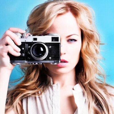 Quadro belo fotógrafo loura segurando câmera retro