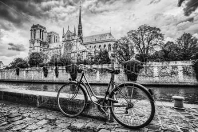 Quadro Bicicleta retrô ao lado da Catedral de Notre Dame em Paris, França e o rio Sena. Vintage preto e branco