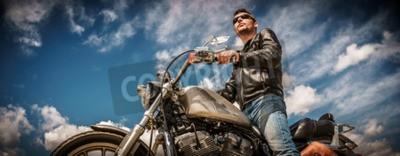 Quadro Biker usando uma jaqueta de couro e óculos de sol sentados em sua motocicleta.
