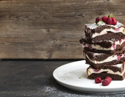 Quadro Brownies-cheesecake tower with raspberries on white plate