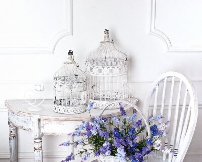 Quadro cadeira do vintage e mesa com flores em frente e gaiolas