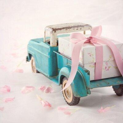 Quadro Caminhão de brinquedo antigo velho carregando uma caixa de presente com fita rosa