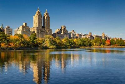 Quadro Central Park e Manhattan, Upper West Side com folhagem de outono colorido. Um céu azul desobstruído e edifícios do Central Park que refletem ocidental no reservatório de Jacqueline Kennedy Onassis. Ci