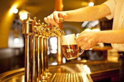 Quadro cerveja do ouro na mão e cerveja torneiras