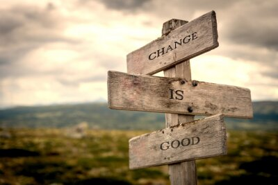 Quadro Change is good quote on wooden signpost in nature with moody background. Motivational, move on, changes, choice, choices concept.