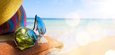 Quadro Chapéu de palha, bolsa e óculos de sol em uma praia tropical