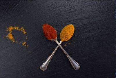 Quadro Duas colheres do vintage com especiarias curry e paprika no fundo preto.