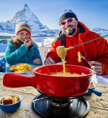 Quadro Esquiadores em um restaurante, Fondue, prato suíço tradicional - Matterhorn em Alpes suíços em segundo plano