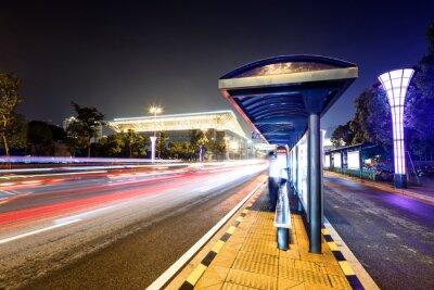 Quadro estação de ônibus ao lado de uma estrada à noite