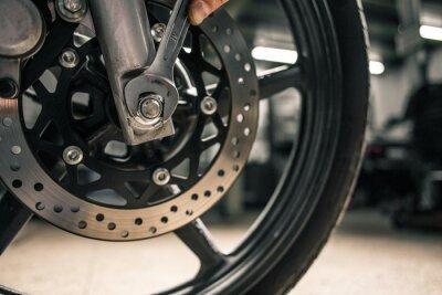 Quadro Feche a mão da mão do homem segurando a chave de montagem perto do veículo da motocicleta.