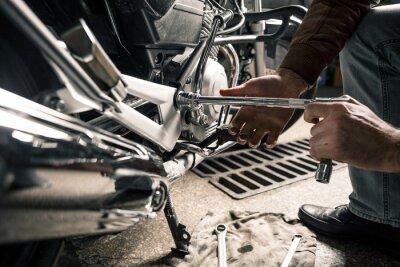 Quadro Feche acima das mãos do homem com motocicleta na garagem