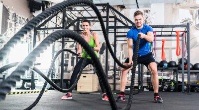 Quadro Frau und Mann em Fitnessstudio com corda de batalha