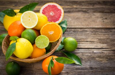 Quadro Fresh and juicy citrus fruits in the basket on the rustic table