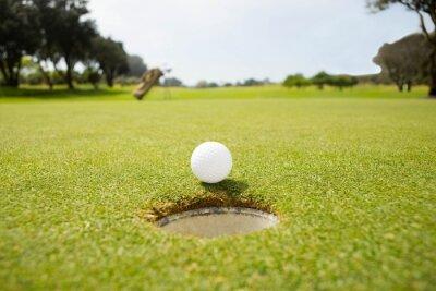 Quadro Golf ball at the edge of the hole