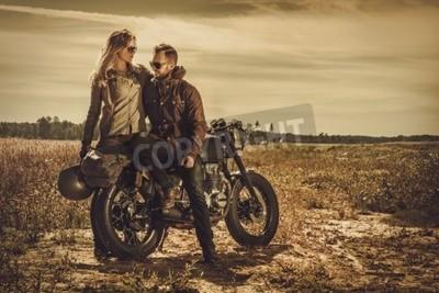 Quadro Jovem e elegante casal de corridas de café nas motocicletas personalizadas vintage em um campo.