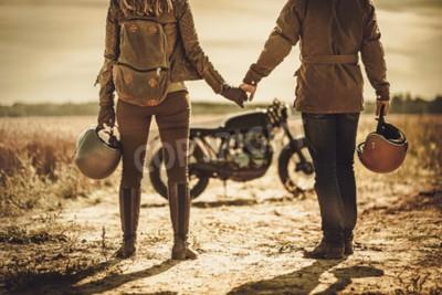 Quadro Jovem, elegante casal de corridas de café nas motocicletas vintage personalizadas em um campo.