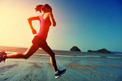 Quadro jovem mulher correndo na praia do nascer do sol
