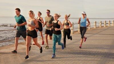 Quadro Jovens correndo ao longo do calçadão da praia