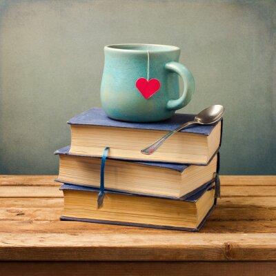 Quadro Livros antigos velhos e copo com formato de coração na tabela de madeira