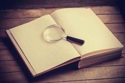 Quadro Loupa e livro sobre a mesa de madeira