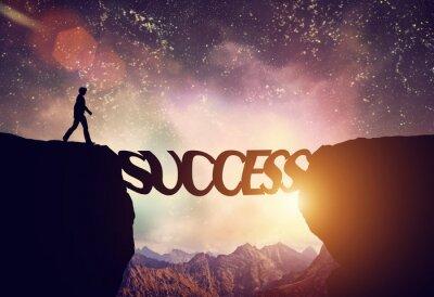 Quadro Man about to walk over precipice on SUCCESS word bridge