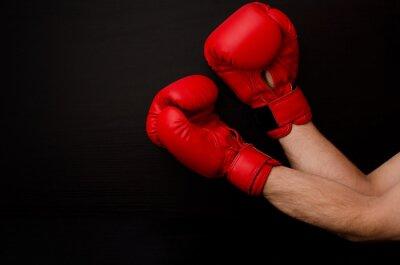 Quadro Mão em luvas de boxe vermelho no canto do quadro sobre um fundo preto, espaço vazio