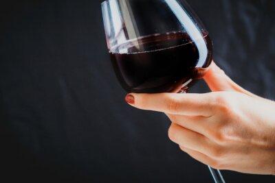Quadro Mão segurando copo de vinho tinto sobre fundo cinza escuro