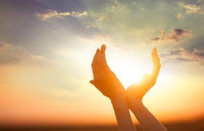 Quadro mãos segurando o sol ao amanhecer