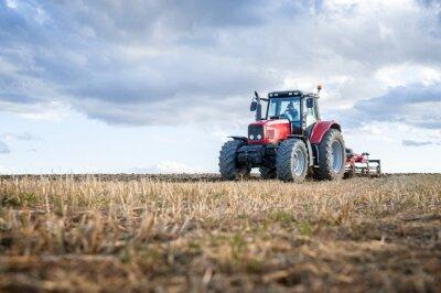 Quadro Máquinas agrícolas em primeiro plano que realizam trabalhos no campo.
