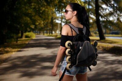 Quadro Menina bonita morena com mochila às costas em que patins