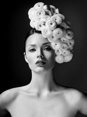 Quadro modelo de moda com grande penteado e flores no cabelo.