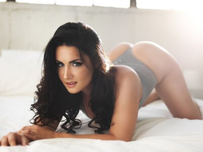 Quadro Modelo sexy na cama brilhantemente iluminada na pose erótica
