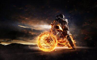 Quadro Motociclista escuro permanecendo na moto em chamas no pôr-do-sol