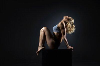 Quadro Mulher apta nova bonita com o corpo muscular magro no sportswear que faz o exercício do esporte. Comprimento total, vista lateral, tiro do estúdio, fundo preto.