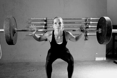 Quadro mulher em uma sessão de levantamento de peso - treino crossfit.