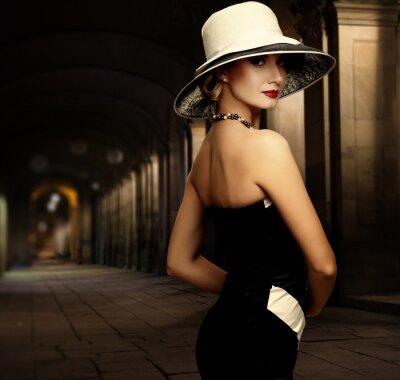 Quadro Mulher no vestido preto e chapéu branco grande sozinho ao ar livre à noite