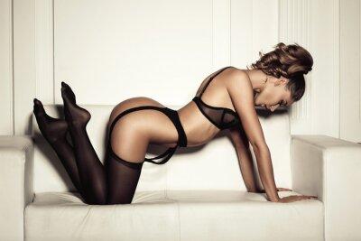 Quadro Mulher sexy na roupa interior preta sedutora sentado em um sofá em sto