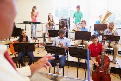 Quadro Os alunos que jogam instrumentos musicais na orquestra Escola