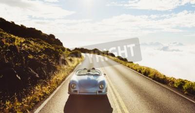 Quadro Pares felizes que conduzem na estrada secundária no Carro de esportes clássico do vintage