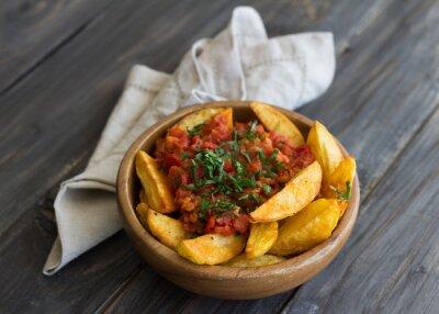 Quadro Patatas bravas, tradicionais tapas espanholas, batatas assadas com molho de tomate picante na bacia de madeira na tabela de madeira. Foco Diferencial