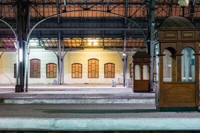 Quadro Plataforma de passageiros durante a noite na estação ferroviária. Estação de trem à noite.