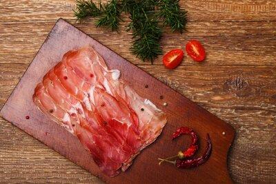 Quadro Presunto delicioso do prosciutto em uma placa de madeira com especiarias.