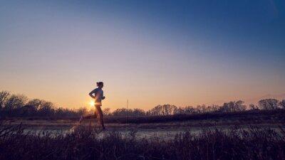 Quadro Ragazza atletica allena all'aperto su terra di sera