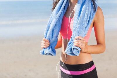 Quadro Seção meados da mulher saudável com uma toalha em volta do pescoço na praia
