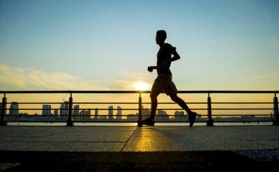 Quadro Silhueta de corredores correndo ao pôr do sol na frente da skyline da cidade